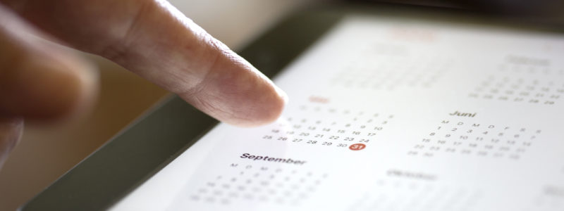 Image shows someone scrolling through a calendar on a tablet.